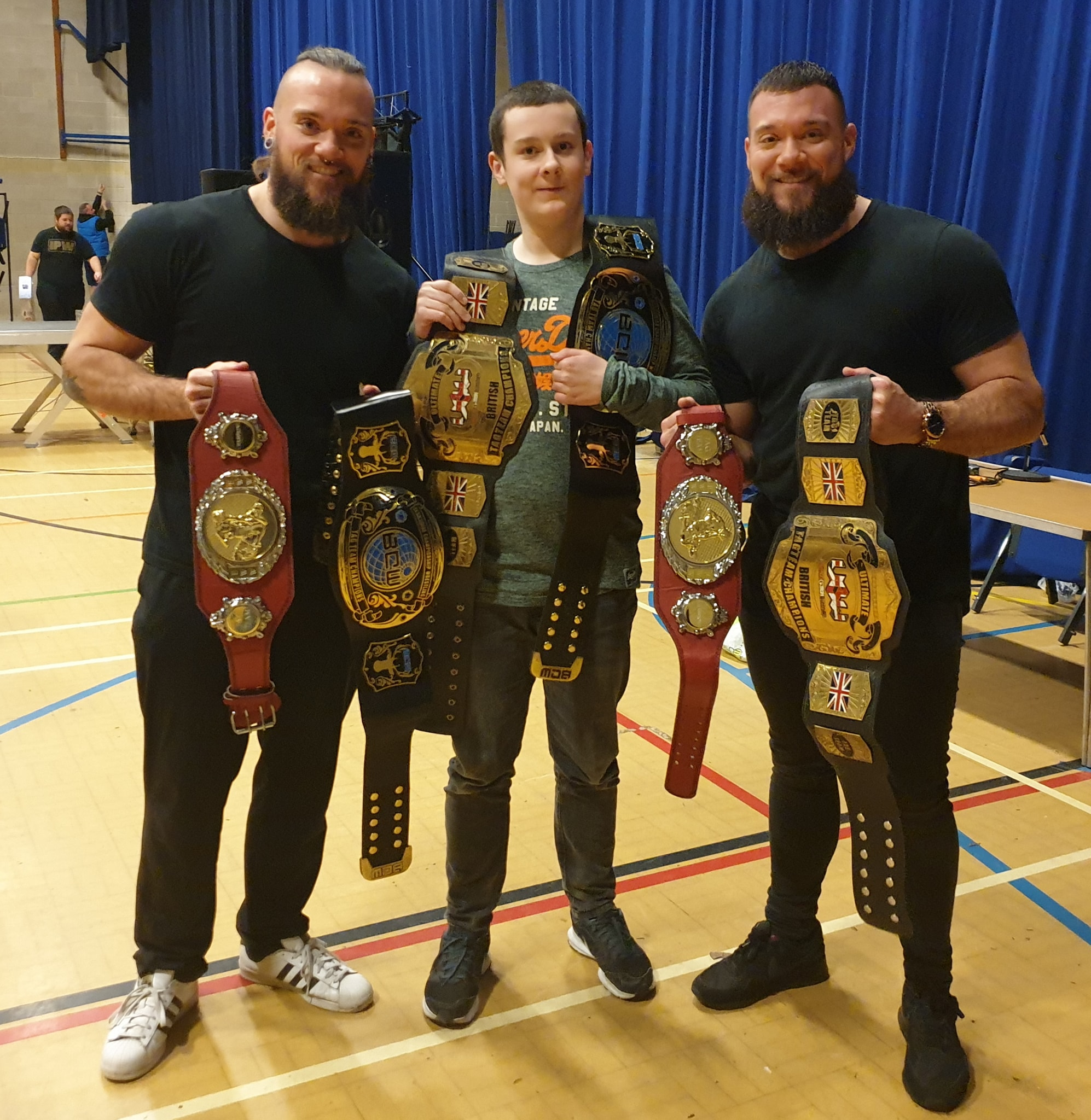 The Bone Brothers having picture taken with a fan and carrying 3 tag titles!